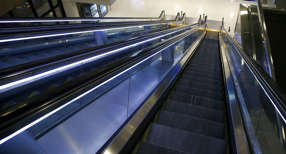 Empty escalators go down to the baggage claim area at Phoenix Sky Harbor International Airport Tuesday, April 14, 2020, in Phoenix. The coronavirus has caused a significant decrease in air travel. (AP Photo/Ross D. Franklin)