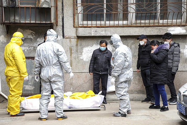 In this Feb. 1, 2020, file photo, funeral home workers remove the body of a person suspected to have died from the coronavirus outbreak from a residential building in Wuhan in central China's Hubei Province. The central Chinese city of Wuhan has raised its number of COVID-19 fatalities by more than 1,000. State media said the undercount had been due to the insufficient admission capabilities at overwhelmed medical facilities at the peak of the outbreak. (Chinatopix via AP, File)