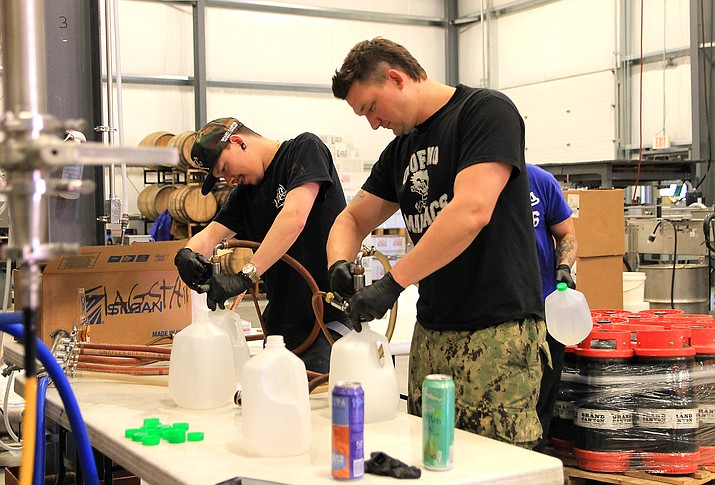 Grand Canyon Brewery employees Ronnie Enriquez, Jacob Maryn and Brandon Walker fill gallon bottles with hand sanitizer April 16 at the Grand Canyon Brewery and Distillery in Williams. (Loretta McKenney/WGCN)