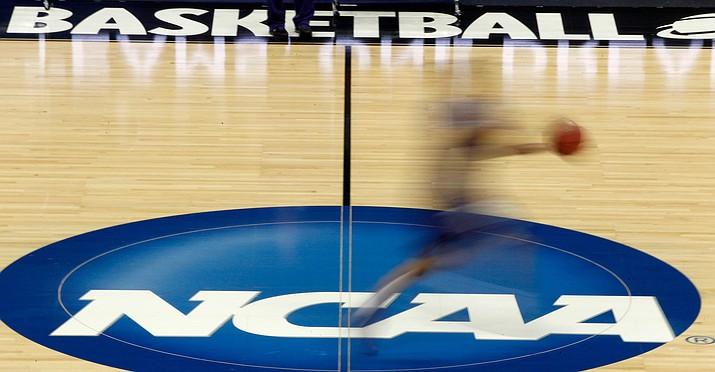 In this March 14, 2012 photo, a player runs across the NCAA logo during practice. The NCAA is moving closer to permitting Division I college athletes to earn money from endorsements and sponsorship deals. (AP file)