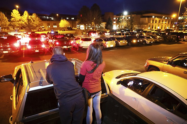 Mike and Kelly Martinez stand in the bed of their pick-up truck as they participate in a prayer gathering in a parking lot at Flagstaff Medical Center to pray for healthcare workers and patients fighting the COVID-19 coronavirus pandemic inside the hospital in Flagstaff, Ariz., on Monday night, April 20, 2020. Since April 1, people have been gathering each night at 7 p.m. led by Pastor Daniel Williamson from Church for the Nations to pray for those inside the hospital. (Jake Bacon/Arizona Daily Sun via AP)