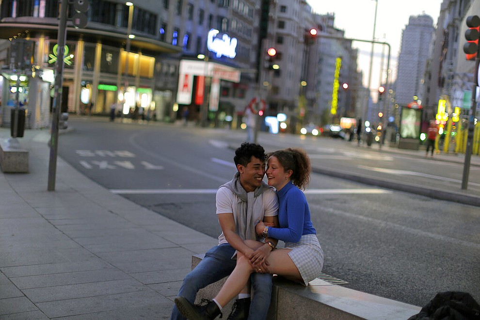 A couple laugh at the Gran Via avenue in downtown in Madrid, Spain, March 14, 2020. (AP Photo/Manu Fernandez)