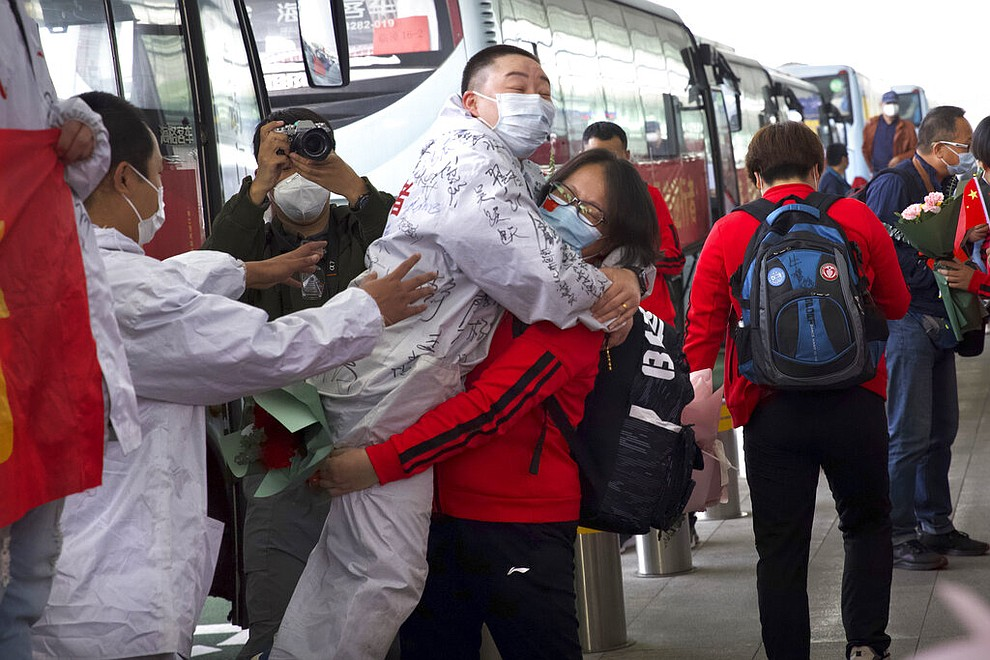 A medical worker from China's Jilin Province, in red, embraces a colleague from Wuhan as she prepares to return home at Wuhan Tianhe International Airport in Wuhan in central China's Hubei Province, April 8, 2020. Within hours of China lifting an 11-week lockdown on the central city of Wuhan, tens of thousands people had left the city by train and plane alone, according to local media reports. (AP Photo/Ng Han Guan)