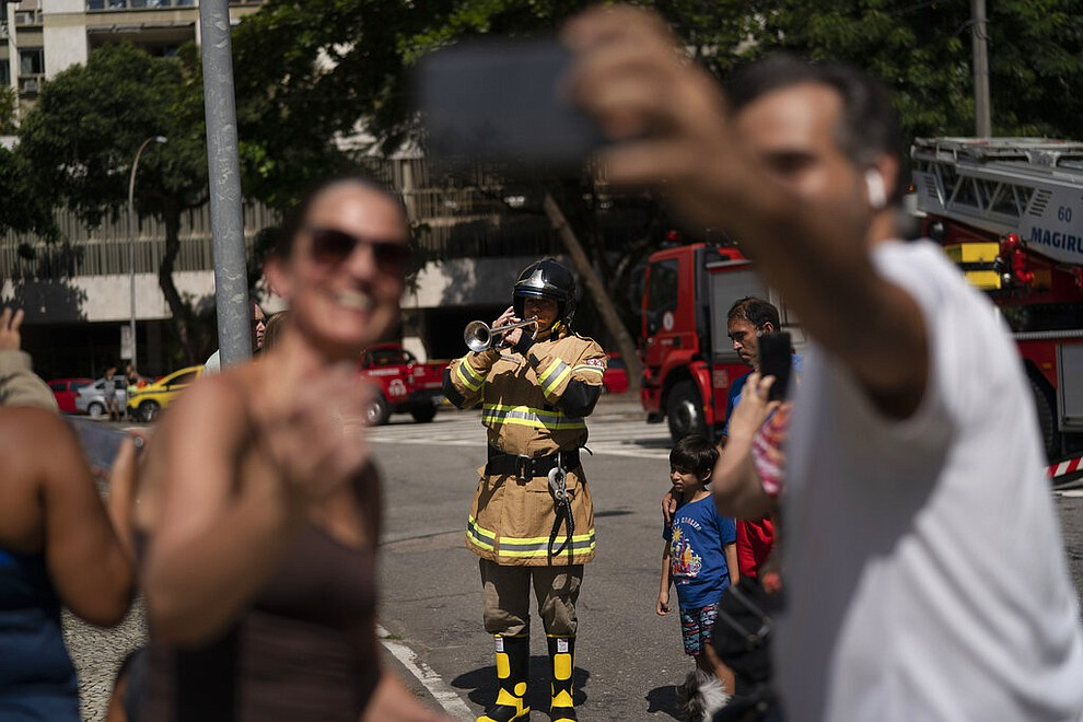 Residents take a selfie with the firefighter Elielson Silva playing his trumpet, after he performed from the top of a very tall ladder for residents cooped up at home during a lockdown to help contain the spread of the new coronavirus in Rio de Janeiro, Brazil, April 5, 2020. (AP Photo/Leo Correa)