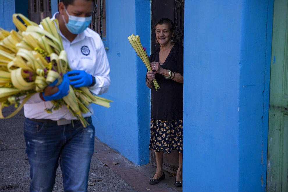 A woman smiles after receiving a palm frond from a Cristo Rey brotherhood member during Palm Sunday in Guatemala City, April 5, 2020. (AP Photo/Moises Castillo)