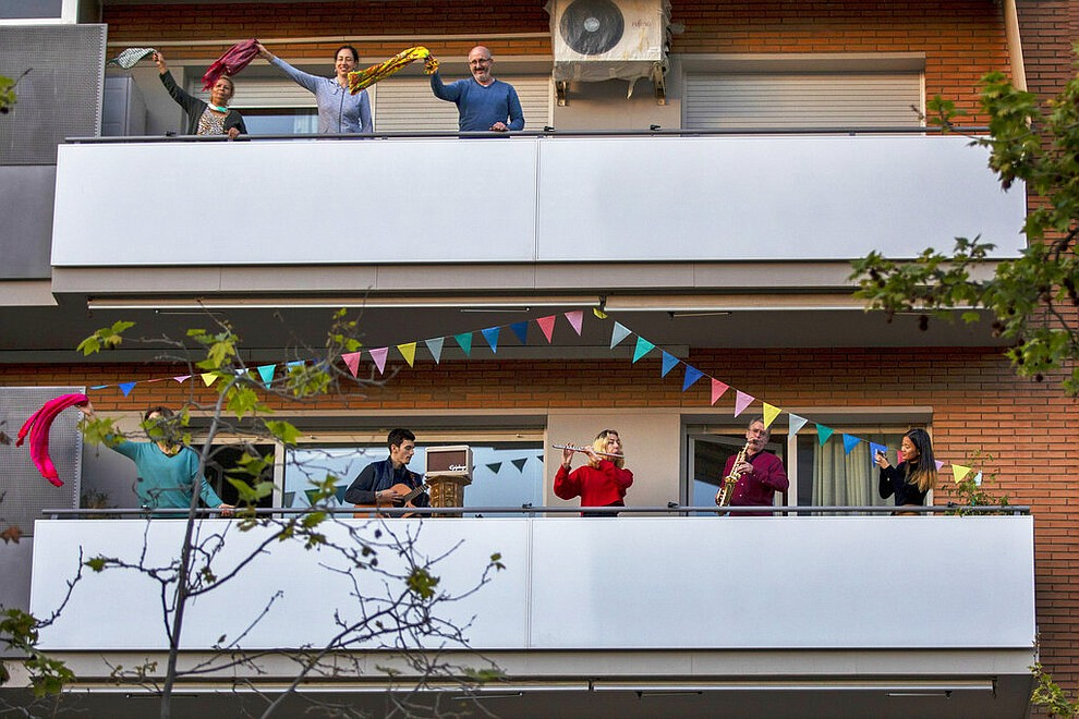 People play instruments as others dance on their balconies in support of the medical staff that are working on the COVID-19 virus outbreak in Barcelona, Spain, April 5, 2020. (AP Photo/Emilio Morenatti, File)