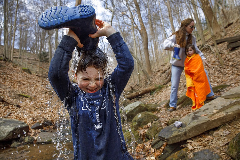 "Desmond Peskowitz, 7, of Takoma Park, Md., pours a stream of water on his head from his boot, March 17, 2020, as he plays a game he called ""champagne fight,"" inspired by Formula 1 Racing, with his mother Kathleen Caulfield, and sister Erin Peskowitz, 4, in Rock Creek Park in Washington. Desmond's school is closed due to coronavirus precautions, and his mother said the park was their ""PE class"" today. ""I don't worry as much about germs when they're outside,"" says Caulfield, ""the touching seems to be less when kids play outdoors."" (AP Photo/Jacquelyn Martin)"