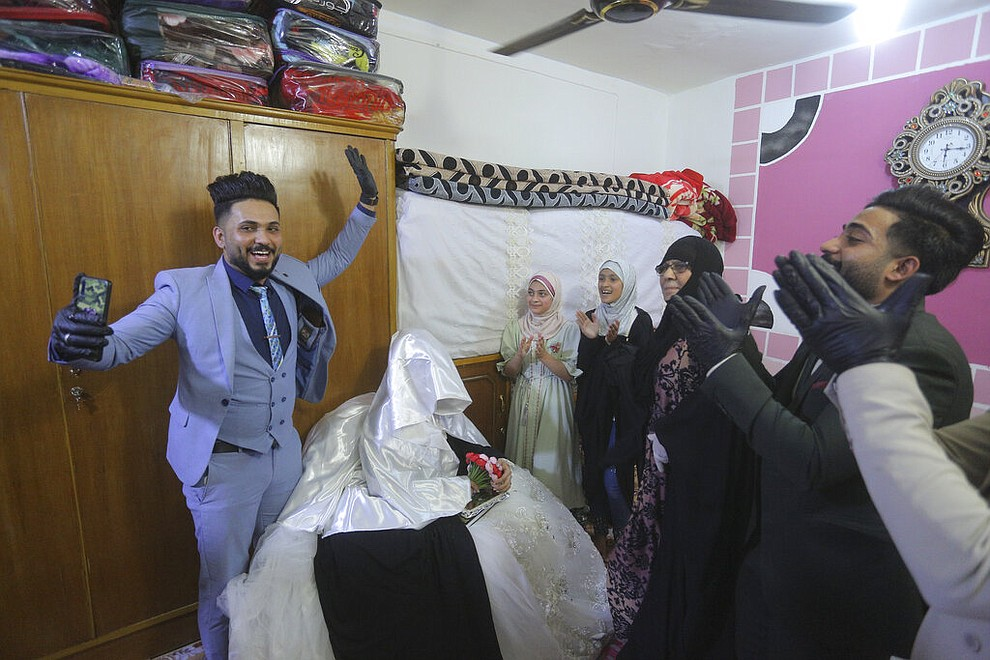 Ahmed Khaled al-Kaabi and his bride Ruqaya Rahim celebrate their wedding in Najaf, Iraq, April 9, 2020, the hardest hit town by coronavirus in the country where government banned large public gatherings. Unwilling to postpone the wedding, al-Kaabi asked the local security forces to help him wed his beloved. The police responded by providing the groom vehicles blasting music to bring his bride to the family home for a small celebration of just six people. (AP Photo/Anmar Khalil)