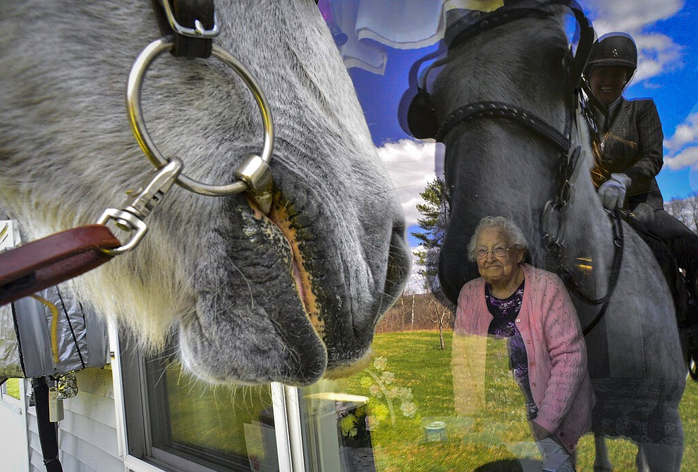 A resident of Vernon Green Nursing Home, in Vernon, Vt., looks out her window as Lisa Tyler, owner of Forever Dream Drafts, visits the nursing home with her horse to try to bring a smile to the faces of the residents and staff members April 15, 2020. The nursing home is sheltering-in-place because of the COVID-19 pandemic to help prevent the residents from contracting the virus. (Kristopher Radder/The Brattleboro Reformer via AP)