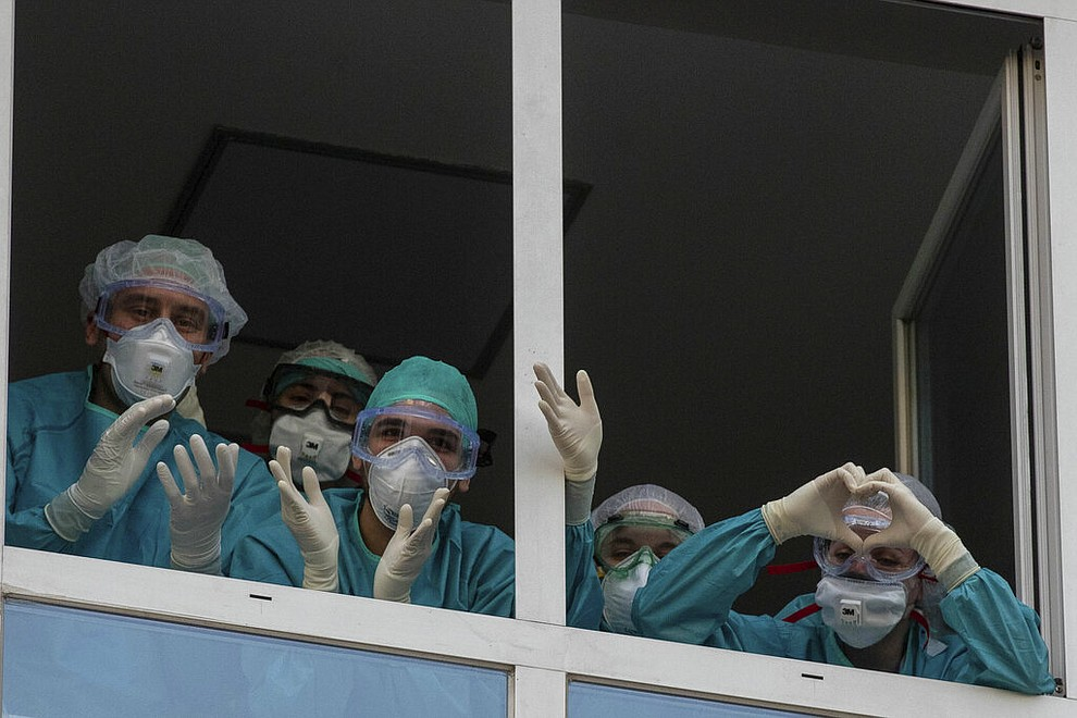 Health workers react as people applaud from their nearby houses in support of the medical staff that are working on the COVID-19 virus outbreak at the Jimenez Diaz Foundation University Hospital in Madrid, Spain, April 15, 2020. (AP Photo/Manu Fernandez)