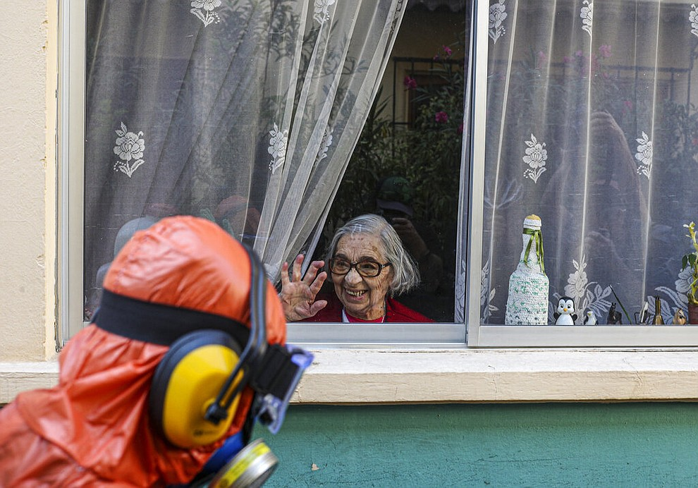 A woman waves to a city worker dressed in a hazmat suit as he disinfects the streets in her neighborhood as a precaution against the spread of the new coronavirus, in Santiago, Chile, April 15, 2020. (AP Photo/Esteban Felix)