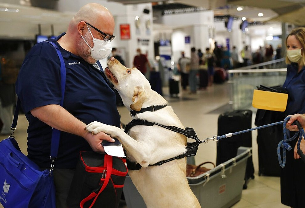 Dr. Rubinstein gets a greeting from a fellow American passenger's dog, named Dumas, as people prepare to board a flight to Miami, Fla., from the Silvio Pettirossi airport in Luque, on the outskirts of Asuncion, Paraguay, April 23, 2020. (AP Photo/Jorge Saenz)