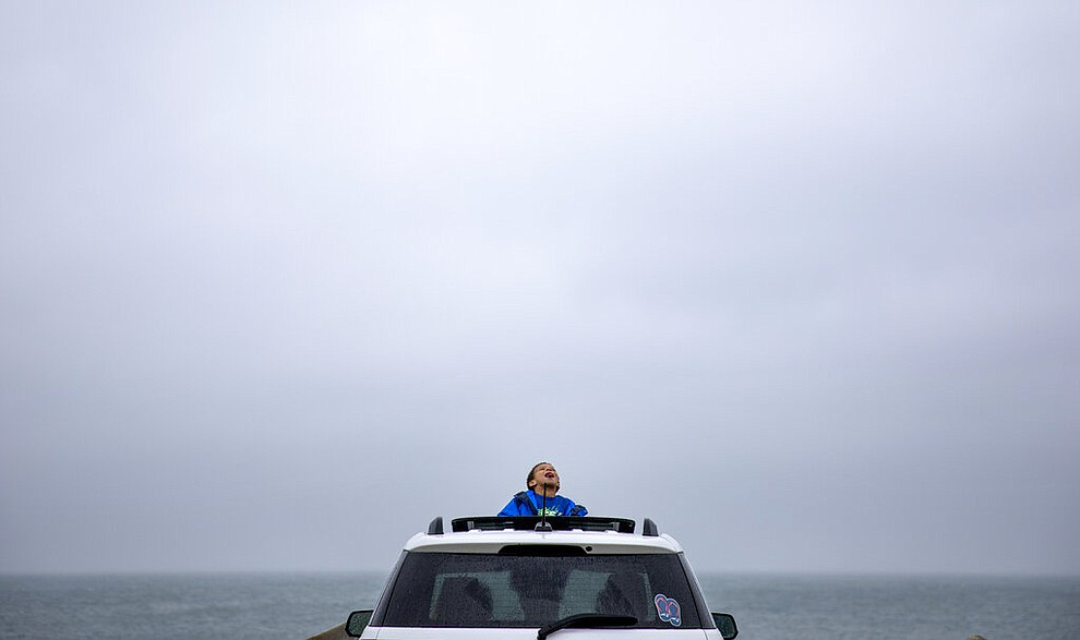 Mason Lambert, 5, looks up at the rain as he leaves the house with his grandmother Karen Lambert, in car at left, and mother Emilie Lambert, right, for his daily outing to one of the few public parking areas still open by the sea during the coronavirus shutdown, April 24, 2020, in Narragansett, R.I. (AP Photo/David Goldman)