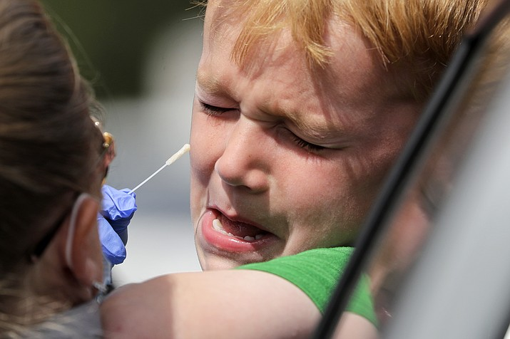 Alex Rodgers, 6, cries and tries to squirm away from a medical assistant attempting to take a swab sample up his nose at a drive-thru coronavirus testing site Wednesday, April 29, 2020, in Seattle. For the next three Saturdays from 8 a.m. to 4 p.m. Spectrum Healthcare will be participating in the blitz at its Prescott location, 990 Willow Creek Road; YRMC is also participating in the Blitz. There will be a free COVID-19 drive-thru testing clinic in Prescott Valley from 9 a.m. to 3 p.m. on May 2 at the YRMC Del E. Webb Outpatient Center, 3262 N. Windsong Drive. (Elaine Thompson/AP)