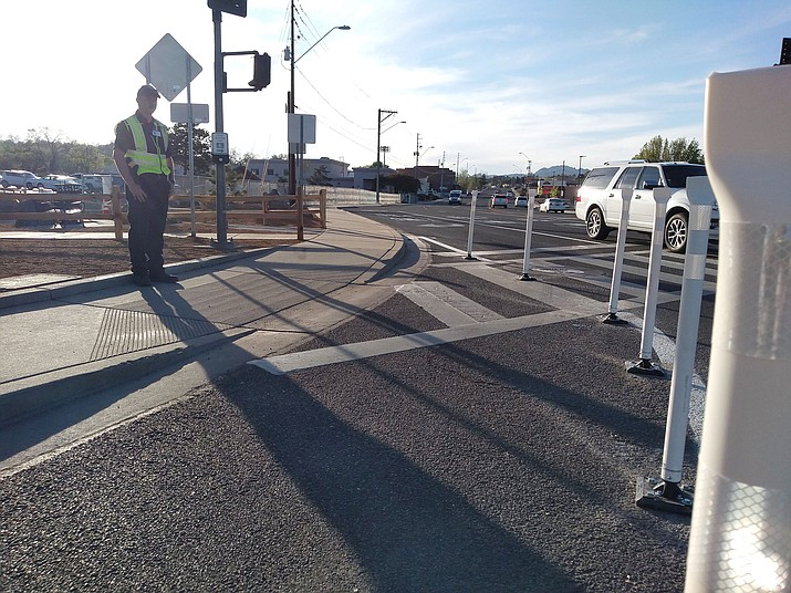 Security Officer Cameron Atkins stands on the corner of Iron Springs Road and Miller Valley Road, in front of new, flexible bollards, to help pedestrians cross safely on Thursday, April 30, 2020. (Jesse Bertel/Courier)