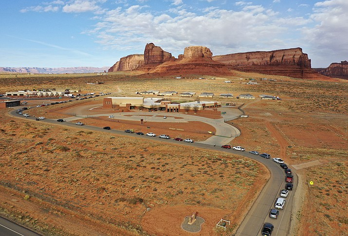 Vehicles line up for COVID-19 testing outside of the Monument Valley Health Center in Oljato-Monument Valley, San Juan County, on Friday, April 17, 2020. More than a thousand people got tested over the course of two days. The Navajo Nation has one of the highest per capita COVID-19 infection rates in the country. (Kristin Murphy/The Deseret News via AP)