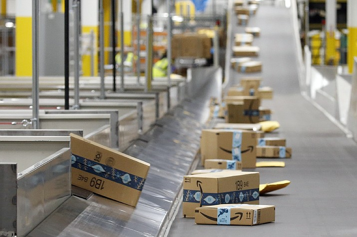 In this Dec. 17, 2019, file photo, Amazon packages move along a conveyor at an Amazon warehouse facility in Goodyear, Ariz. Amazon will report quarterly earnings on Thursday, April 30, providing a first glimpse into its financial performance during the pandemic. (AP Photo/Ross D. Franklin, File)