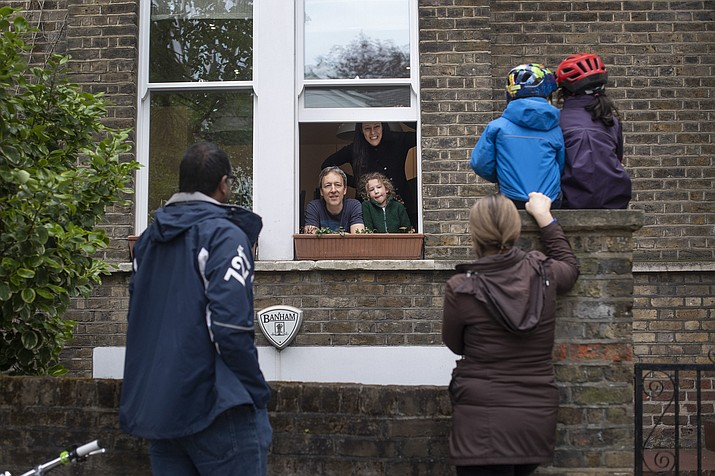 Two families who gave permission to be photographed, maintain social distancing while talking to each other outside a home in Hampstead, north London, Sunday May 3, 2020, as the UK continues in lockdown to help curb the spread of the coronavirus. The highly contagious COVID-19 coronavirus has impacted on nations around the globe, many imposing self isolation and exercising social distancing when people move from their homes. (Victoria Jones/PA via AP)
