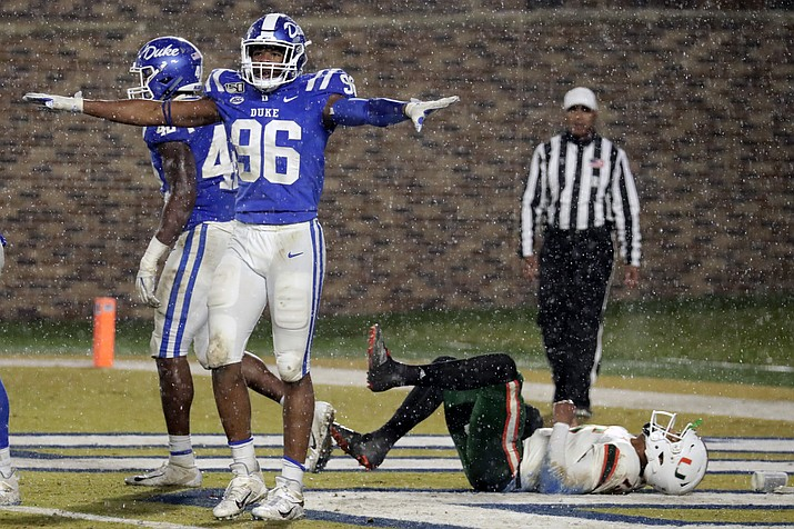 In this Nov. 30, 2019 file photo, Duke's Chris Rumph II (96) celebrates in front of Miami's Jarren Williams (15) after Duke made a defensive stop during the third quarter of an NCAA college football game in Durham, N.C. Football players and other college athletes are facing challenges when it comes to following nutrition plans amid the coronavirus pandemic. Rumph has been staying with family and eating home-cooked meals as he tries to gain strength amid the pandemic that has shut down college and professional sports. (Chris Seward/AP, file)