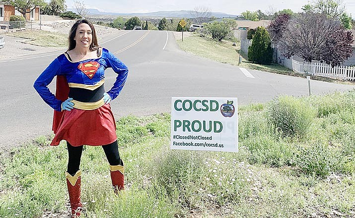 """Sara Bowers, a sixth grade mathematics teacher at Dr. Daniel Bright Elementary School, stands next to one of the signs Cottonwood-Oak Creek educators have posted around the community to remind students how badly they are missed. Said Sarah Rogers, paraprofessional for the school's fifth grade and sixth grade, Bowers """"embodies the super hero in all teachers.""""Photo courtesy Cottonwood-Oak Creek School District"""