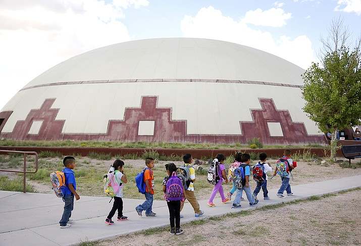 Students walk between buildings at the Little Singer Community School in Birdsprings, Ariz., on the Navajo Nation. The tribe is among plaintiffs in a federal lawsuit that seeks to keep the U.S. Treasury Department from disbursing coronavirus relief funding for tribes to Alaska Native corporations. (AP Photo/John Locher, File)