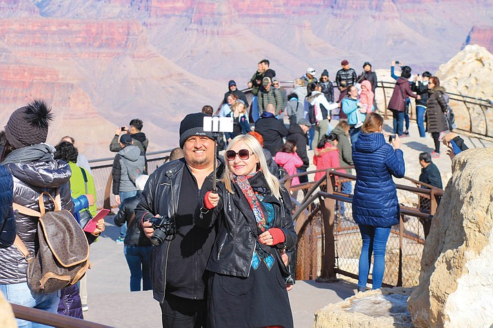 Tourists pose for a selfie in 2018. Parks around the country are grappling with how best to expand service while preserving the pristine nature. One of the latest debates is playing out at the Grand Canyon where park officials are road mapping future telecommunications towers. The handful that exist now are prominent among the park lodging, visitor center and residential area. (Loretta McKenney/WGCN)