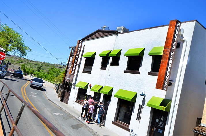 A family walks by the Haunted Hamburger in Jerome on Tuesday but turns around when they find out its closed. However, the popular restaurant opens for take-out on Friday and in-restaurant dining on Monday. VVN/Vyto Starinskas