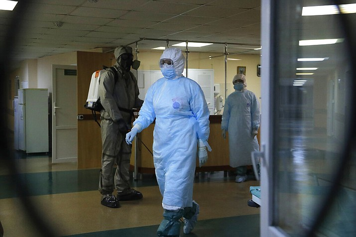 A serviceman of Belarus Ministry of Defence, left, and medical workers wearing protective gear are seen at a local hospital in Minsk, Belarus, Tuesday, May 5, 2020. Despite the World Health Organization's call for Belarus to ban public events as coronavirus cases rise sharply, President Alexander Lukashenko says the country will go ahead with a parade to mark the 75th anniversary of the defeat of Nazi Germany. (AP Photo/Sergei Grits)