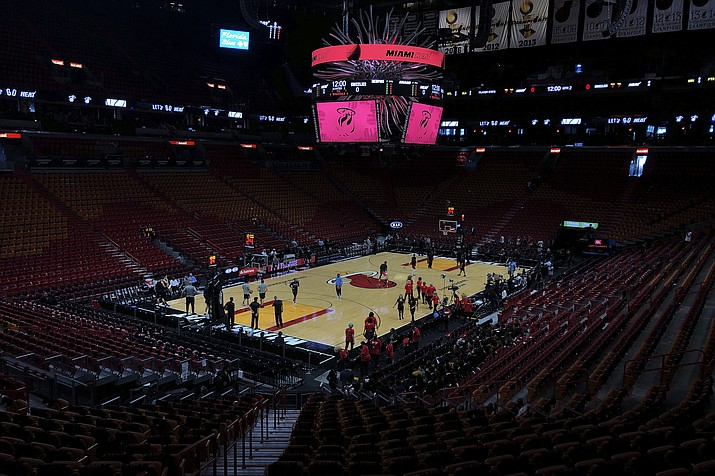 In this Oct. 23, 2019, file photo, the Miami Heat and the Memphis Grizzlies practice before an NBA basketball game in Miami, Fla. If so inclined, NBA teams like Miami, Orlando and Utah could all be back in the gym for voluntary workouts in small groups starting Friday when the league ban on such things expires. None of them will be reopening that day. There's a clear desire for basketball to resume but, perhaps mindful of how rushing back too quickly hurt other leagues around the world, the NBA seems to be taking very cautious baby steps back to the court. (Brynn Anderson/AP, file)