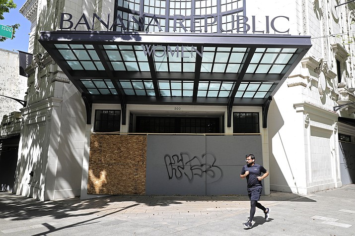 A person jogs past a boarded up and closed Banana Republic clothing store in downtown Seattle. The U.S. unemployment rate hit 14.7 percent in April, the highest rate since the Great Depression, as 20.5 million jobs vanished in the worst monthly loss on record. The figures are stark evidence of the damage the coronavirus has done to a now-shattered economy. (AP Photo/Ted S. Warren)