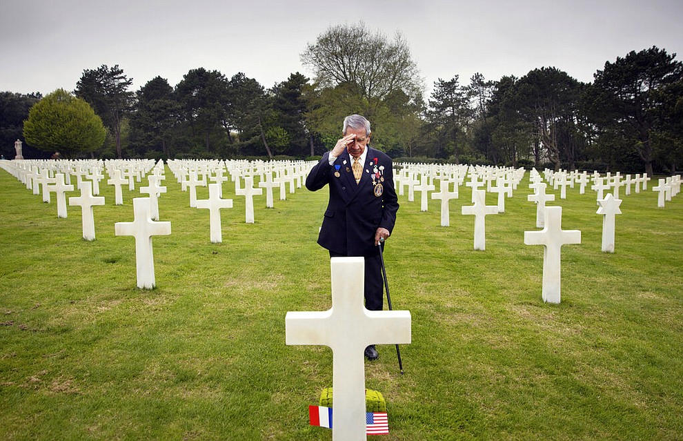 In this May 1, 2019 file photo, World War II and D-Day veteran Charles Norman Shay, from Indian Island, Maine, salutes the grave of fellow soldier Edward Morozewicz at the Normandy American Cemetery in Colleville-sur-Mer, Normandy, France. Instead of parades, remembrances, embraces and one last great hurrah for veteran soldiers who are mostly in their nineties to celebrate VE Day, it is instead a lockdown due to the coronavirus, COVID-19. (AP Photo/Virginia Mayo, File)