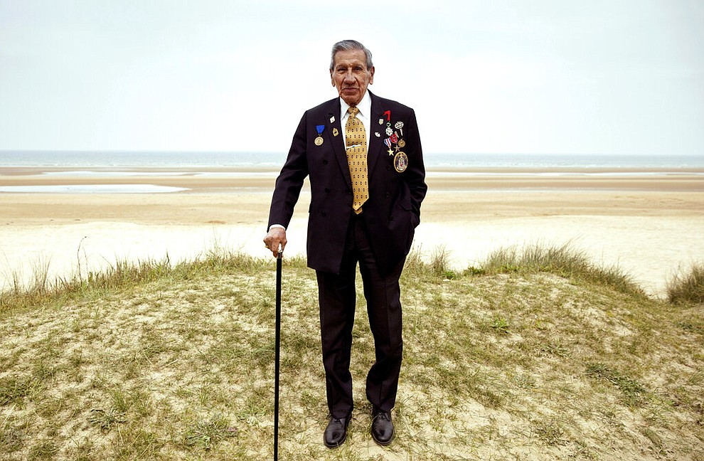 In this Wednesday, May 1, 2019 file photo, World War II and D-Day veteran Charles Norman Shay, from Maine, poses at the Charles Shay monument on Omaha Beach in Normandy, France. Instead of parades, remembrances, embraces and one last great hurrah for veteran soldiers who are mostly in their nineties to celebrate VE Day, it is instead a lockdown due to the coronavirus, COVID-19. (AP Photo/Virginia Mayo, File)
