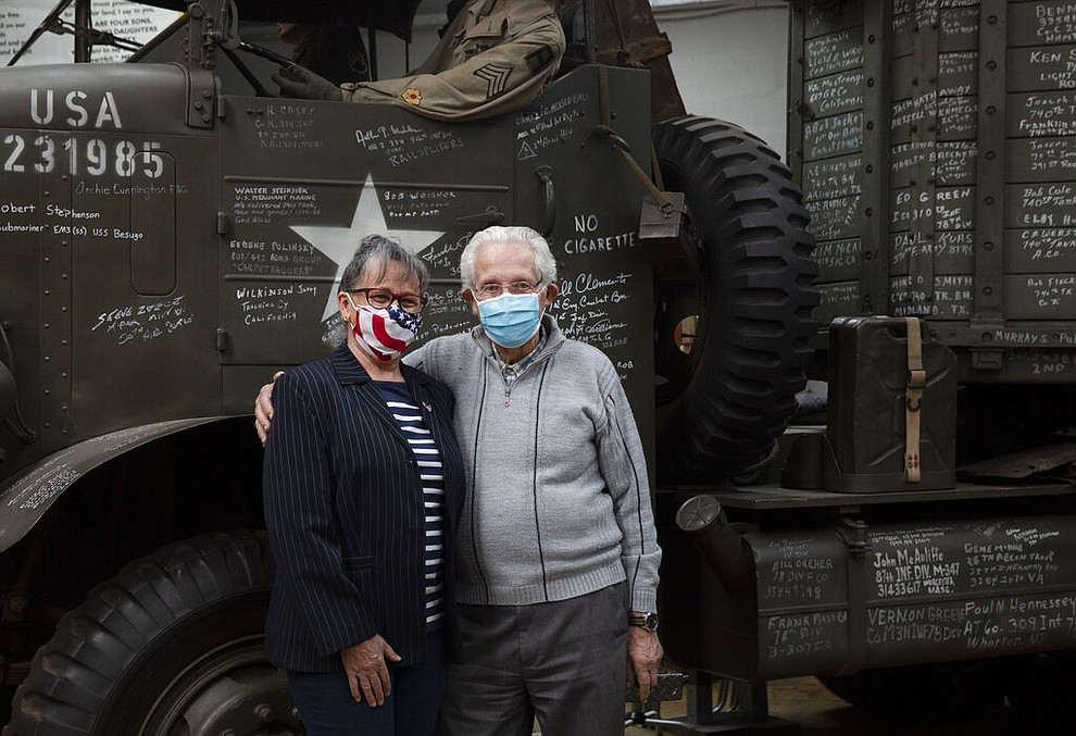 In this photo taken on Tuesday, May 5, 2020, directors of the Remember Museum 39-45, Marcel Schmetz, right, and Mathilde Schmetz pose in front of a World War II vintage truck with their mouth masks on in Thimister-Clermont, Belgium. The couple run a war museum, right where the Battle of the Bulge, Hitler's last stand to change the tide of the war, took place. But what was supposed to be the highlight of the year is now spent in isolation with Mathilde behind closed doors of the museum. (AP Photo/Virginia Mayo)