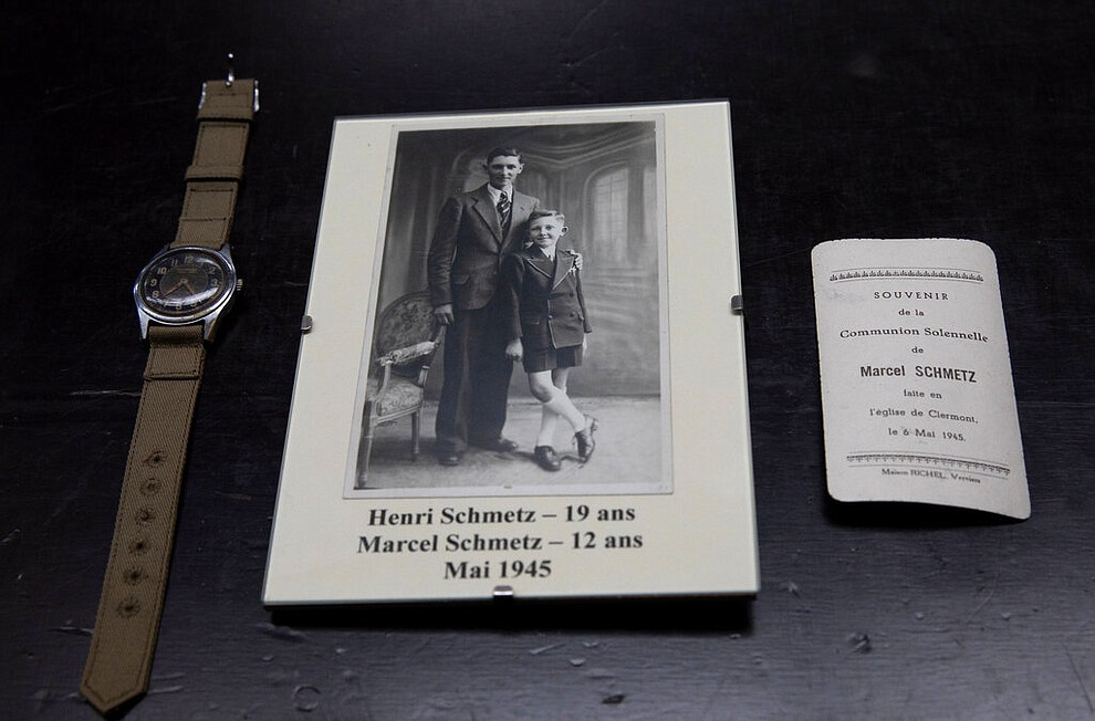 In this photo taken on Tuesday, May 5, 2020, a photo of brothers Henri Schmetz and Marcel Schmetz, is placed next to a watch given to Marcel Schmetz from and American WWII soldier at the Remember Museum 39-45 in Thimister-Clermont, Belgium. Schmetz now runs a war museum with his wife Mathilde, right where the Battle of the Bulge, Hitler's last stand to change the tide of the war, took place. But what was supposed to be the highlight of the year is now spent in isolation with Mathilde behind closed doors of the museum. (AP Photo/Virginia Mayo)