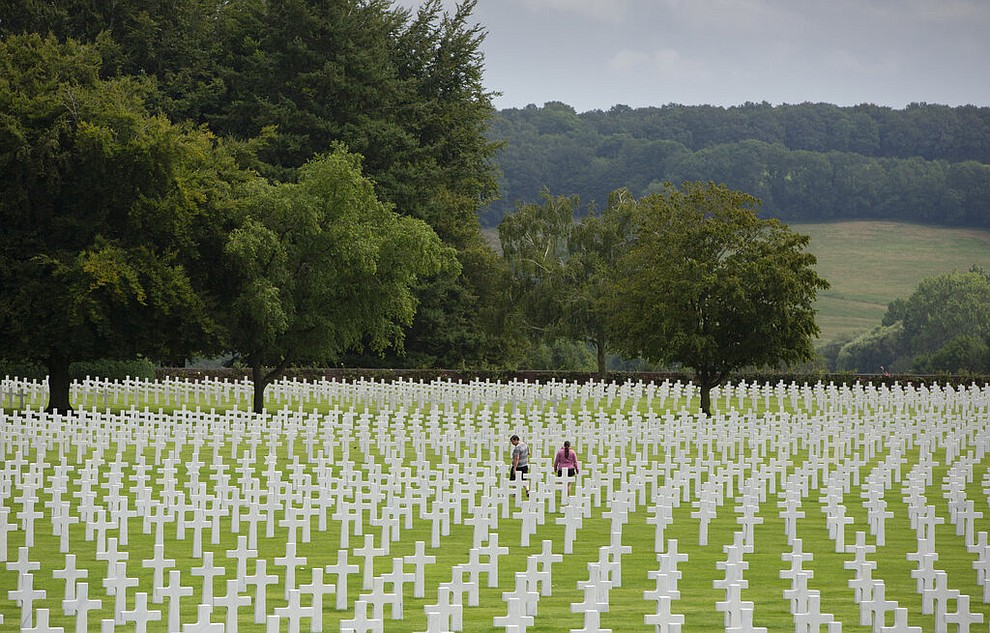 In this Aug. 8, 2019 file photo, visitors walk among the headstones at the Henri Chapelle World War II cemetery in Henri Chapelle, Belgium. The cemetery contains 7,992 American war dead and covers 57 acres. Due to coronavirus concerns American war cemeteries are currently closed in Belgium. (AP Photo/Virginia Mayo, File)