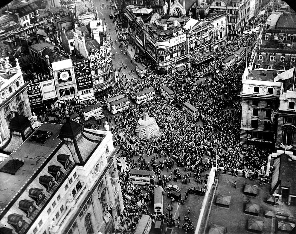 FILE - In this May 8, 1945 file photo a crowd gathers to celebrate VE Day in Piccadilly Circus in London, England. On Friday's 75th anniversary of the end of World War II in Europe, talk of war is afoot again — this time against a disease that has killed at least a quarter of a million people worldwide. Instead of parades, remembrances and one last great hurrah for veterans now mostly in their nineties, it is a time of lockdown and loneliness, with memories bitter and sweet (AP Photo, File)