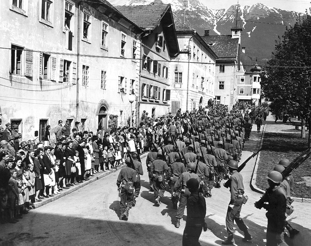 FILE - In this May 8, 1945 file photo the 44th Infantry Division, U.S. Seventh Army, parades on VE Day through the town square of Imst, Austria. On Friday's 75th anniversary of the end of World War II in Europe, talk of war is afoot again — this time against a disease that has killed at least a quarter of a million people worldwide. Instead of parades, remembrances and one last great hurrah for veterans now mostly in their nineties, it is a time of lockdown and loneliness, with memories bitter and sweet (AP Photo, File)
