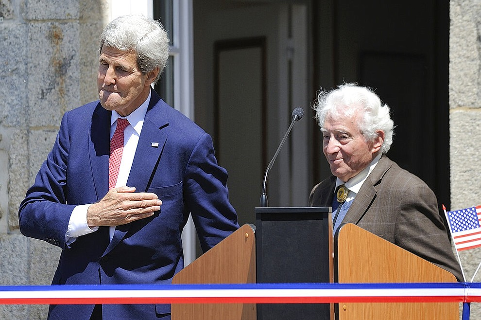 "FILE - In this Saturday, June 7, 2014 file photo US Secretary of State John Kerry and World War II photographer Tony Vaccaro, right, attend the inauguration of the Tony Vaccaro Square, in front of the Saint-Briac-sur-Mer city hall, western France. Vaccaro, 97, was thrown into WWII with the 83rd Infantry division which fought, like Charles Shay, in Normandy, and then came to Schmetz's doorstep for the Battle of the Bulge. On top of his military gear, he also carried a camera, and became a fashion and celebrity photographer after the war. COVID-19 caught up with him last month. Like everything bad life threw at him, he shook it off, attributing his survival to plain ""fortune."" (AP Photo/ Jean Sebastien Evrard, Pool)"