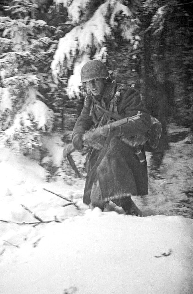 "In this 1944 photo titled ""Hell In Hurtgen"" by photographer Tony Vaccaro, shows an American soldier in Germany's Hurtgen Forest. Vaccaro, 97, was thrown into WWII with the 83rd Infantry division which fought, like Charles Shay, in Normandy, and then came to Schmetz's doorstep for the Battle of the Bulge. On top of his military gear, he also carried a camera, and became a fashion and celebrity photographer after the war. COVID-19 caught up with him last month. Like everything bad life threw at him, he shook it off, attributing his survival to plain ""fortune."" (Photo courtesy Tony Vaccaro via AP)"