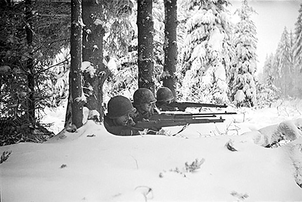 "In this 1944 photo titled ""Firing Line"" by photographer Tony Vaccaro, shows American soldiers in Germany's Hurtgen Forest. Vaccaro, 97, was thrown into WWII with the 83rd Infantry division which fought, like Charles Shay, in Normandy, and then came to Schmetz's doorstep for the Battle of the Bulge. On top of his military gear, he also carried a camera, and became a fashion and celebrity photographer after the war. COVID-19 caught up with him last month. Like everything bad life threw at him, he shook it off, attributing his survival to plain ""fortune."" (Photo courtesy Tony Vaccaro via AP)"