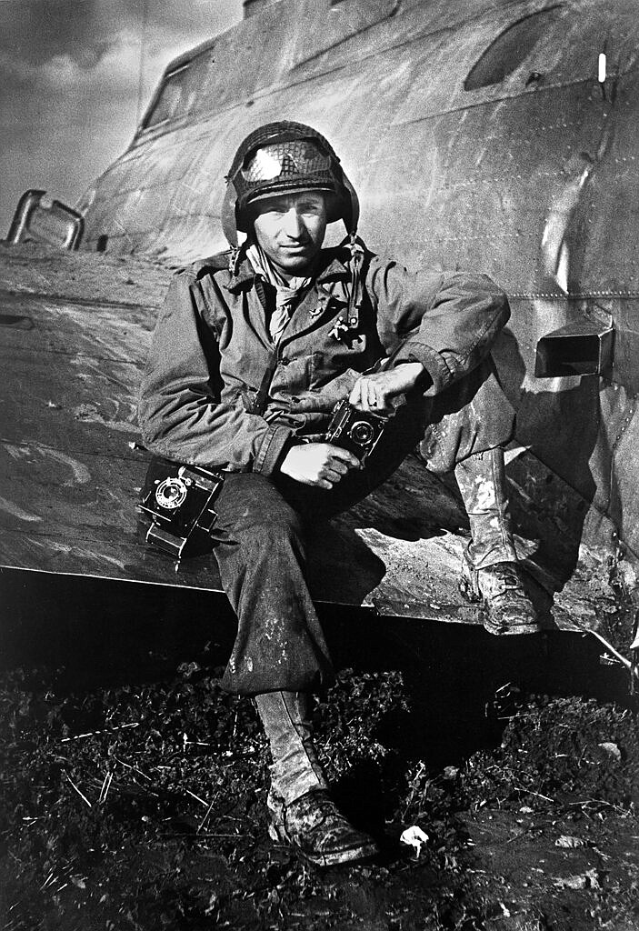 "This 1945 photo shows photographer PFC Tony Vaccaro posing for a photo on the wing of an airplane during WWII. Vaccaro, 97, was thrown into WWII with the 83rd Infantry division which fought, like Charles Shay, in Normandy, and then came to Schmetz's doorstep for the Battle of the Bulge. On top of his military gear, he also carried a camera, and became a fashion and celebrity photographer after the war. COVID-19 caught up with him last month. Like everything bad life threw at him, he shook it off, attributing his survival to plain ""fortune."" (Photo courtesy Tony Vaccaro via AP)"