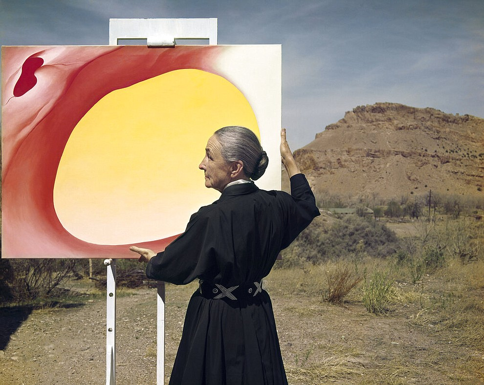 "This 1960 photograph by Tony Vacarro shows artist Georgia O'Keeffe posing with her painting ""Pelvis Series, Red with Yellow"" in Taos Pueblo, New Mexico. Vaccaro, 97, was thrown into WWII with the 83rd Infantry division which fought, like Charles Shay, in Normandy, and then came to Schmetz's doorstep for the Battle of the Bulge. On top of his military gear, he also carried a camera, and became a fashion and celebrity photographer after the war. COVID-19 caught up with him last month. Like everything bad life threw at him, he shook it off, attributing his survival to plain ""fortune."" (Photo courtesy Tony Vaccaro via AP)"