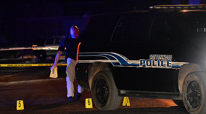 An officer examines a crime scene Wednesday evening near Birch and 15th streets in Cottonwood. A Cottonwood police officer suffered non-life threatening injuries and one person was taken into custody during a Wednesday evening altercation, according to a news release. (Photo/Vyto Starinskas)