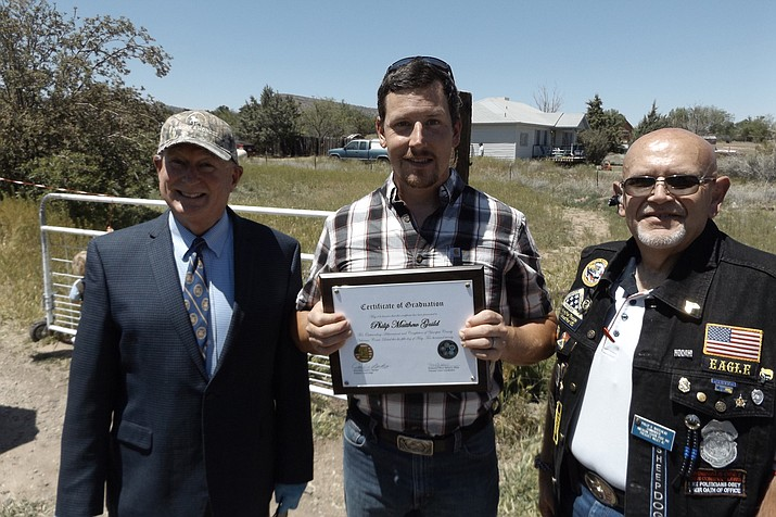 Marine veteran Philip Guild, middle, of Chino Valley holds his certificate and takes a photo with Judge Dave Mackey, right, and American Legion Post 140 of Prescott Valley Commander Philip Whitehead, right, during a drive-by parade that celebrated Guild's graduation from the Veteran's Court redemption program on Tuesday, May 5, 2020, at the Chino Valley Public Library. (Wayne Nelson/Courtesy)
