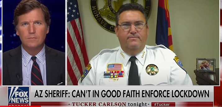 This screenshot captured from YouTube shows Fox News host Tucker Carlson, left, interview Mohave County Sheriff Doug Schuster about his decision not to enforce Gov. Doug Ducey's lockdown orders.