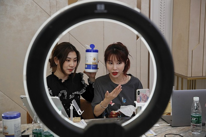 "In this May 5, 2020, photo, China's online celebrity Zhang Mofan, right, introduces the disinfectant wipes to her online clients and fans through the live-streaming at her house in Beijing. Retailers in China are embracing livestreaming as a sales channel amid a Chinese ""shoppertainment"" boom accelerated during the COVID-19 pandemic. Via livestreaming, retailers can interact with customers in real time, while customers make purchases directly in the stream. (AP Photo/Andy Wong)"