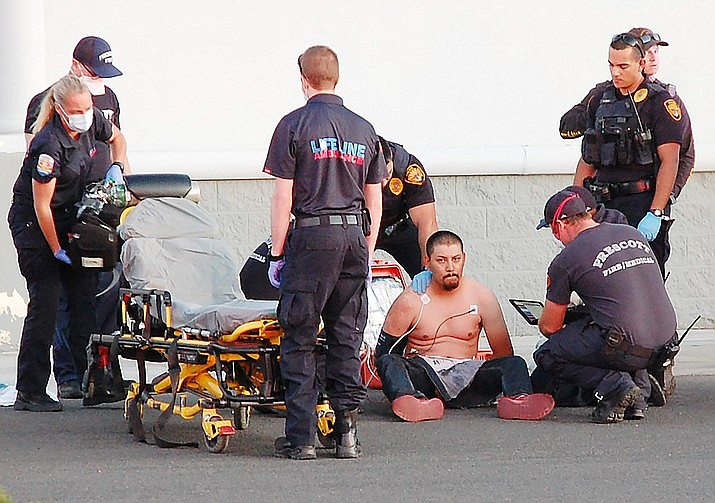 First responders treat a suspect captured by police Wednesday night, May 13, 2020, after he fled from officers at speeds reaching 120 mph, striking cars and possibly firing a gun at officers. (Tim Wiederaenders/Courier)