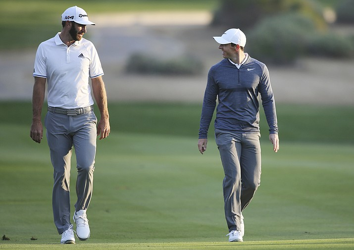 Dustin Johnson, left, and Rory McIlroy talk on the 10th fairway during the 2018 Abu Dhabi Championship golf tournament in Abu Dhabi, United Arab Emirates. (Kamran Jebreili/AP, File)