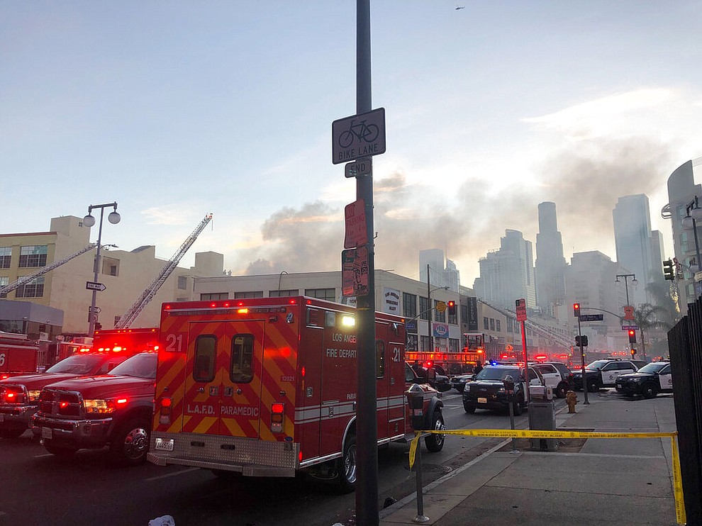 Firefighters and other first responders work the perimeter of an explosion in downtown Los Angeles that has injured multiple firefighters and caused a fire that spread to several buildings, Saturday, May 16, 2020, in Los Angeles. (AP Photo/Stefanie Dazio)