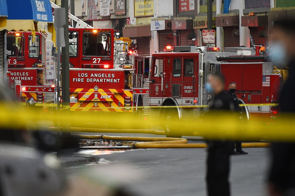 Los Angeles Police Department officers work the scene of a structure fire that injured multiple firefighters, according to a fire department spokesman, Saturday, May 16, 2020, in Los Angeles. (AP Photo/Mark J. Terrill)